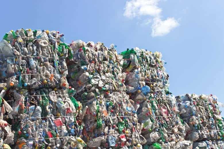 Stacks of compressed plastic ready for recycling, shot against a blue sky