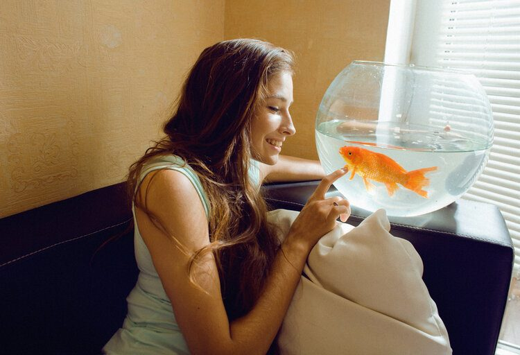woman playing with pet goldfish
